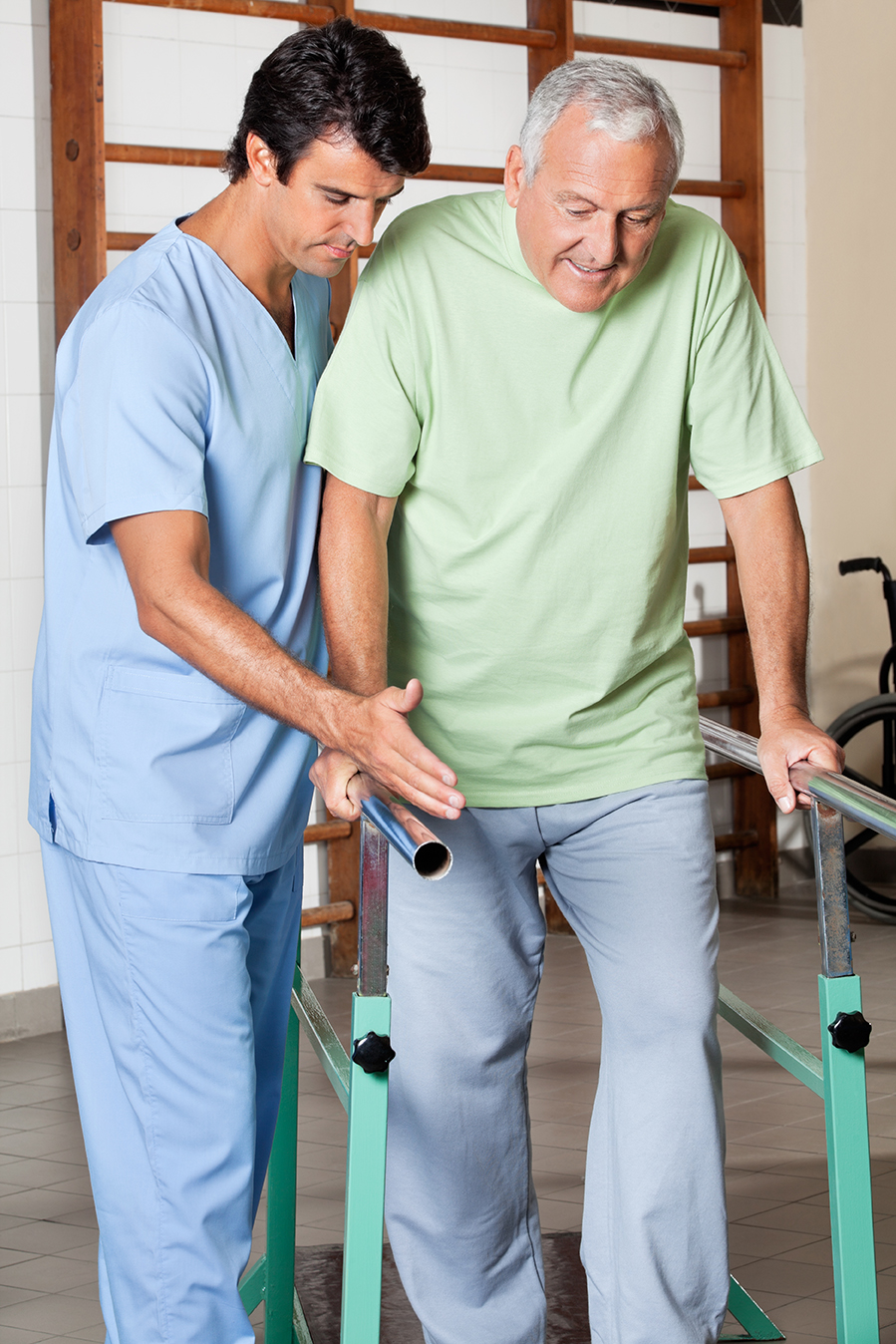 Physical therapist assisting senior man to walk with the support