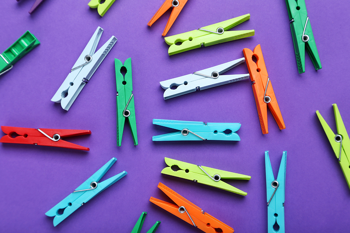 Plastic clothespins on a purple background