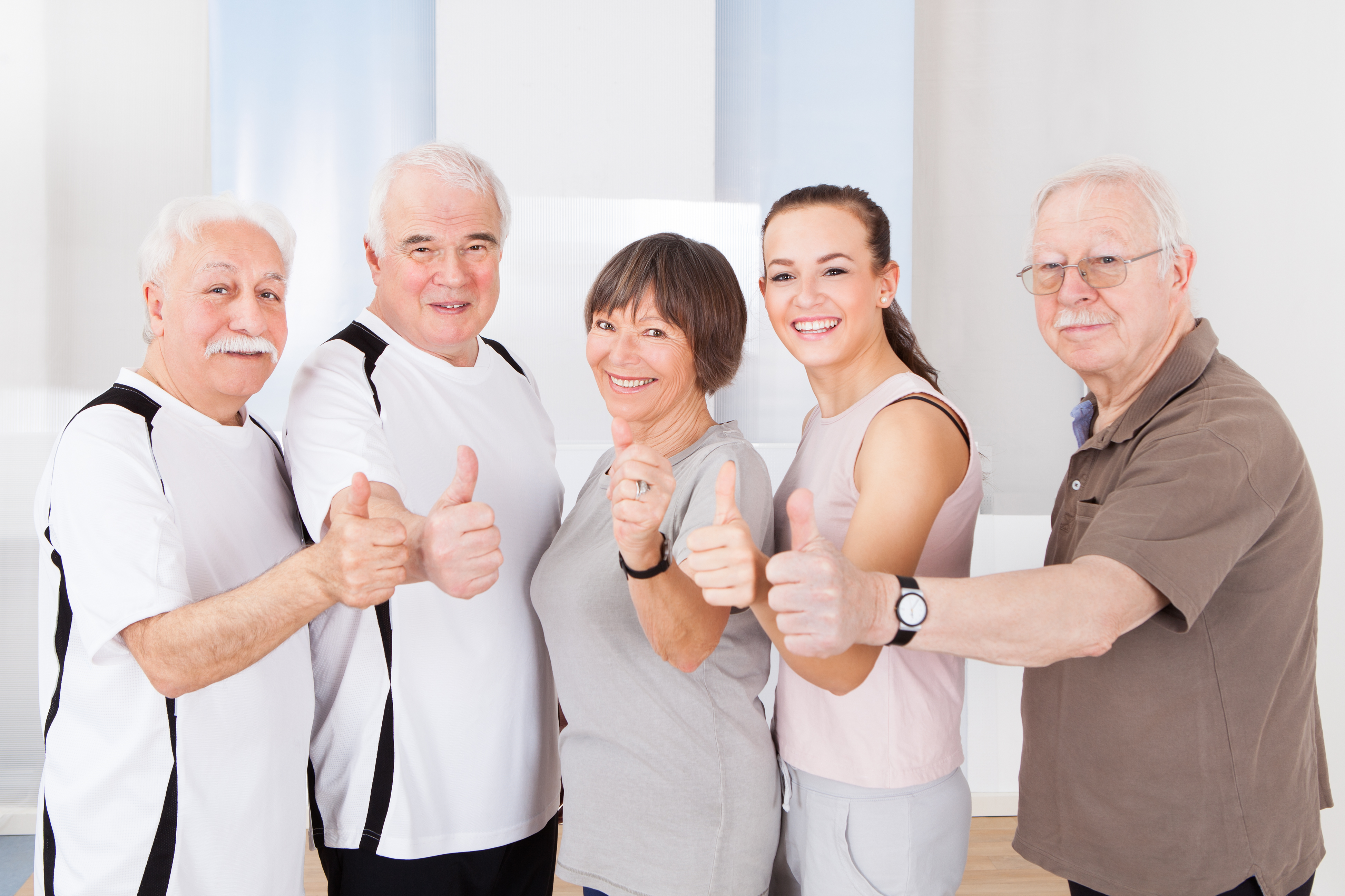 Portrait of confident trainer and senior customers showing thumbs up at healthclub