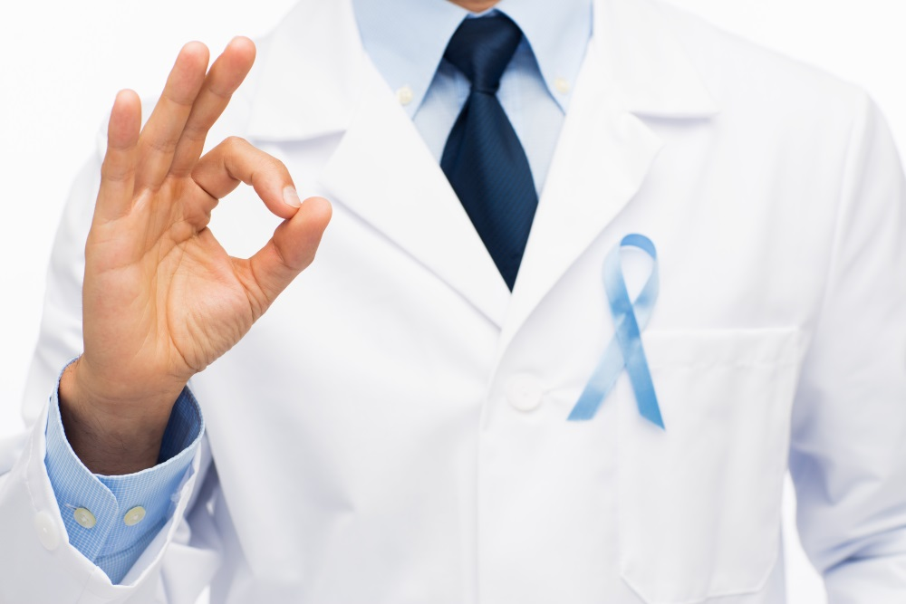 Happy doctor with prostate cancer awareness ribbon