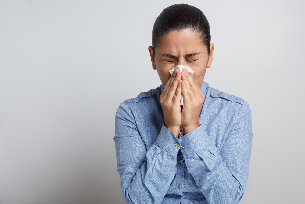 Woman sneezing in tissue