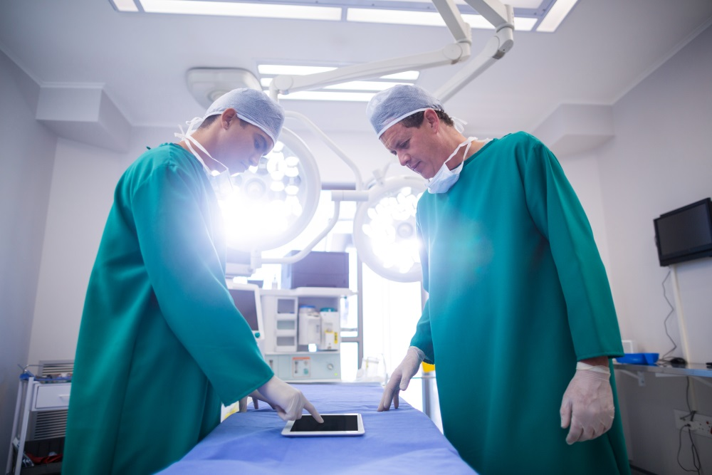 Surgeons using digital tablet in operation