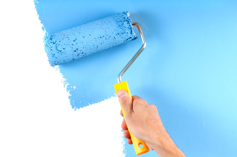Blue color painting wall with roller
