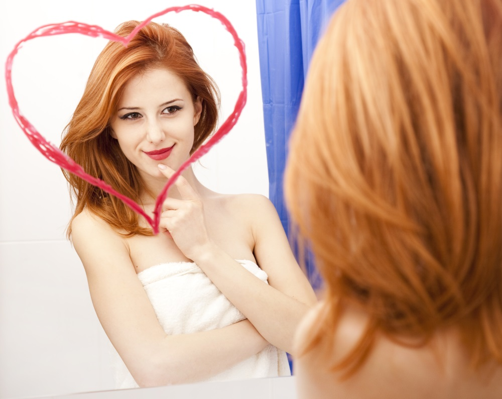 Redhead girl near mirror with heart at it