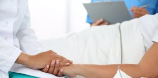 Friendly female doctor's hands holding patient's hand